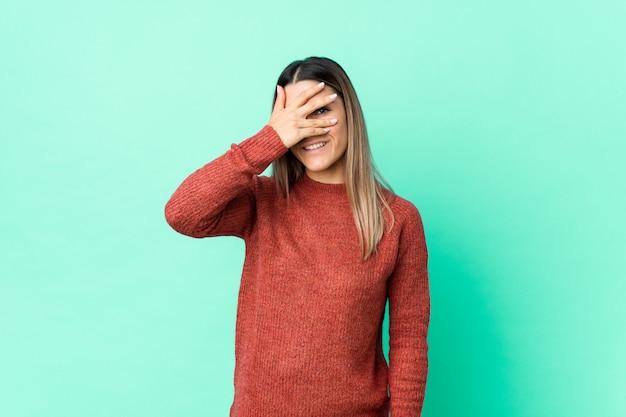 La mujer caucásica joven aislada parpadea en la cámara con los dedos, avergonzado cubriendo la cara.