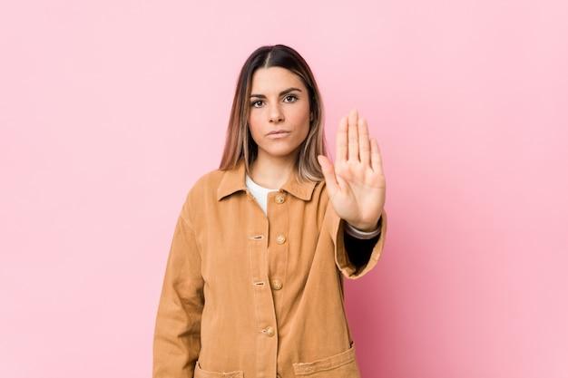Mujer caucásica joven aislada de pie con la mano extendida que muestra la señal de stop, impidiéndole.