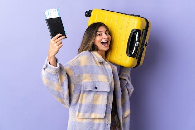 Mujer caucásica joven aislada en púrpura en vacaciones con maleta y pasaporte