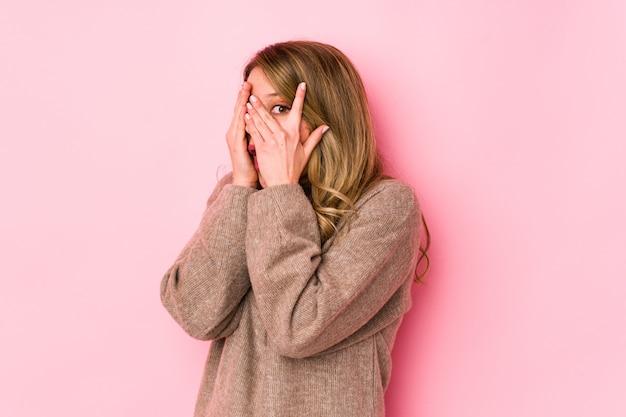 La mujer caucásica joven aislada en rosa parpadea a través de los dedos asustados y nerviosos.