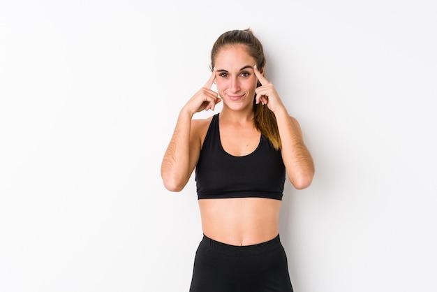 Mujer caucásica joven de la aptitud que presenta en una pared blanca centrada en una tarea, manteniendo los dedos índice que señalan la cabeza.