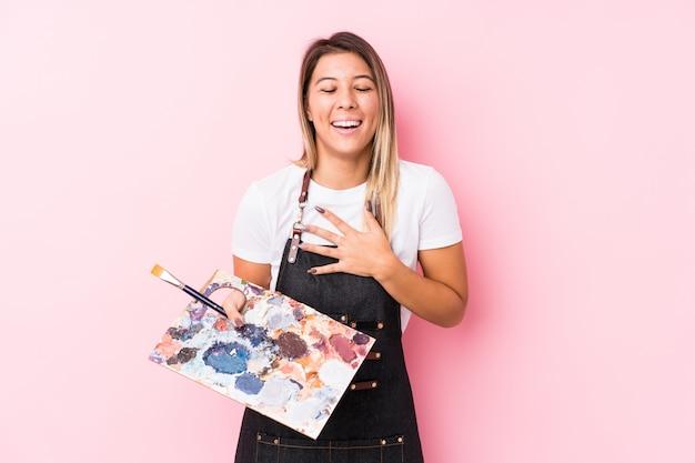 La mujer caucásica joven del artista que sostiene un palett aislado ríe a carcajadas manteniendo la mano en el pecho.