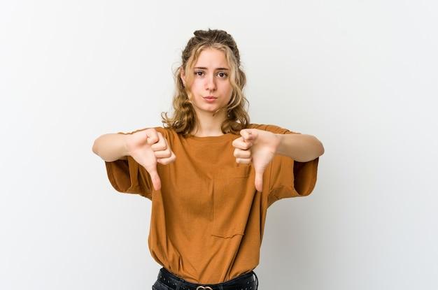 Mujer caucásica joven en el backrgound blanco que muestra el pulgar hacia abajo y que expresa aversión.