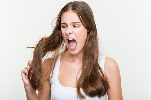 Mujer caucásica joven cepillando su cabello