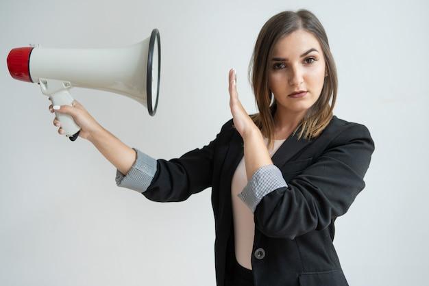 Mujer caucásica joven confiada que dirige el megáfono en sí misma