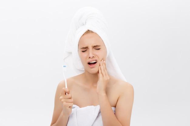 Mujer caucásica joven con dolor de muelas mientras que cepilla sus dientes