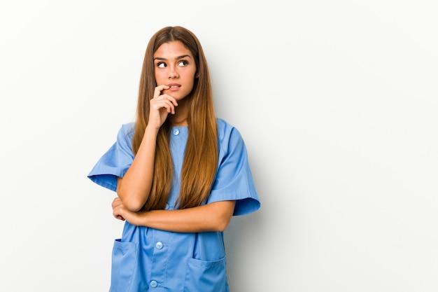 La mujer caucásica joven de la enfermera se relajó pensando en algo que miraba un espacio en blanco.