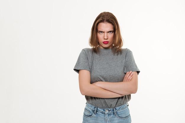 Mujer caucásica joven enojada con los brazos cruzados.