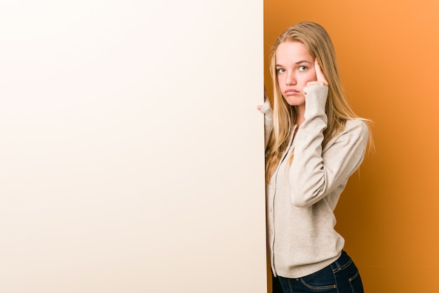 Mujer caucásica joven con espacio de copia apuntando su sien con el dedo, pensando, centrado en una tarea.