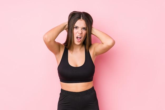 Mujer caucásica joven fitness aislada cubriendo las orejas con las manos tratando de no escuchar un sonido demasiado fuerte.