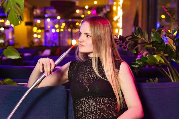 Mujer caucásica joven fuma un narguile o shisha en el club o bar de humo