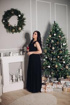 Mujer caucásica joven hermosa con el pelo largo y oscuro en vestido negro largo se encuentra cerca del árbol de navidad antes de la cena