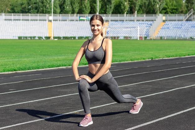 Mujer caucásica joven hermosa que hace ejercicios, calentando y estirando el entrenamiento en estadio corriente.