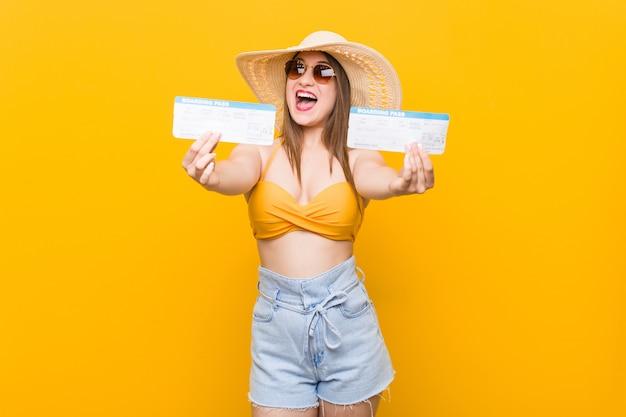 Mujer caucásica joven lista para ir a la playa con boletos aéreos