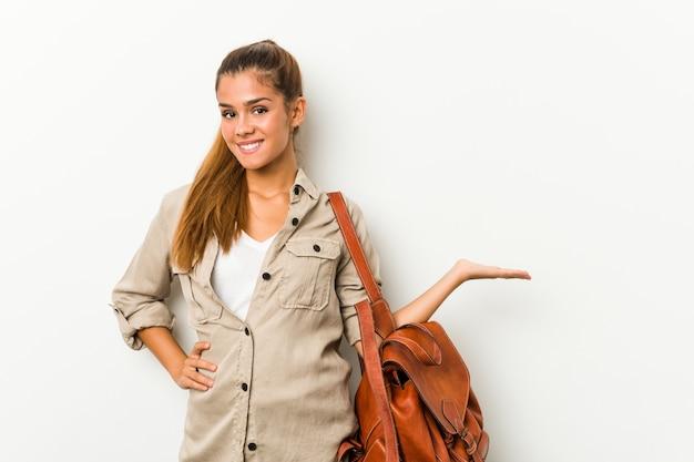 Mujer caucásica joven lista para un viaje que muestra un espacio de la copia en una palma y que lleva a cabo otra mano en la cintura.