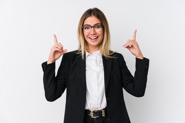 La mujer caucásica joven del negocio indica con ambos dedos delanteros para arriba que muestran un espacio en blanco.