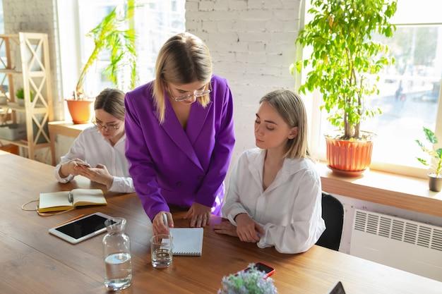 Mujer caucásica joven de negocios en la oficina moderna con equipo