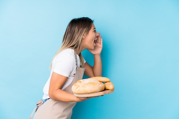 La mujer caucásica joven del panadero aisló gritar y sostener la palma cerca de boca abierta.