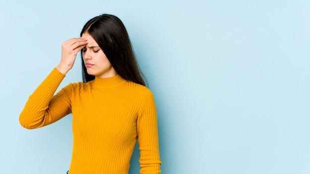 Mujer caucásica joven en la pared azul que tiene un dolor de cabeza, tocando el frente de la cara.