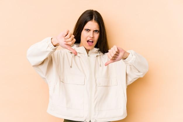 Mujer caucásica joven en la pared beige que muestra el pulgar hacia abajo y que expresa aversión.