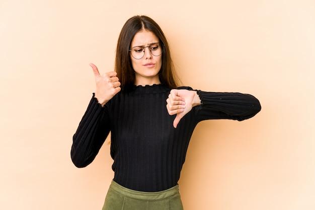 Mujer caucásica joven en la pared beige que muestra los pulgares hacia arriba y hacia abajo