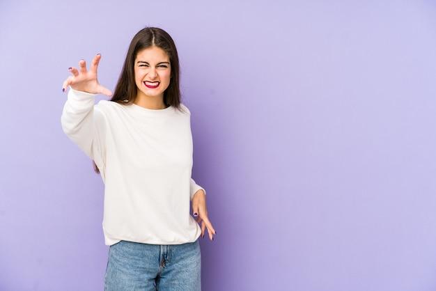 Mujer caucásica joven en la pared púrpura que muestra las garras que imitan un gato, gesto agresivo.