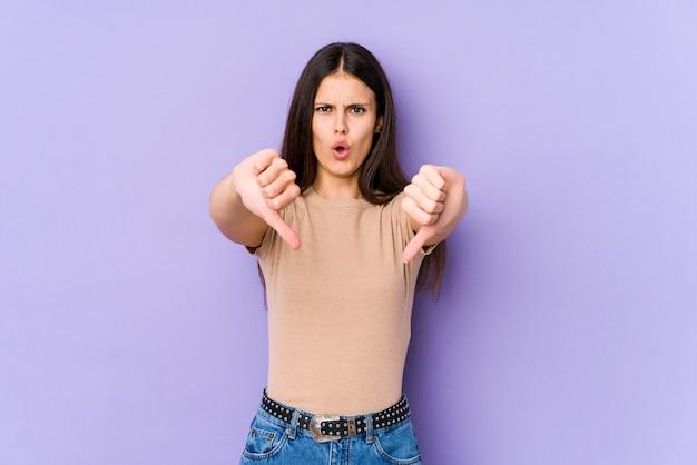 Mujer caucásica joven en la pared púrpura que muestra el pulgar hacia abajo y que expresa aversión.