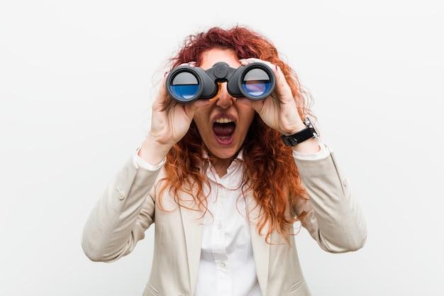 Mujer caucásica joven pelirroja de negocios sosteniendo un binoculares gritando emocionado al frente.