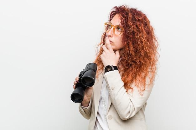 Mujer caucásica joven pelirroja de negocios sosteniendo un binoculares mirando hacia los lados con expresión dudosa y escéptica.