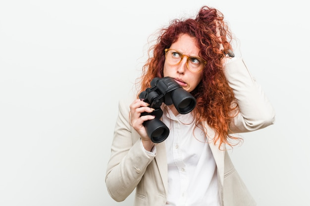 Mujer caucásica joven pelirroja de negocios sosteniendo un binoculares sorprendidos, ha recordado una reunión importante.