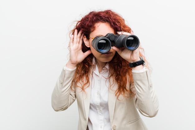 Mujer caucásica joven pelirroja de negocios sosteniendo un binoculares tratando de escuchar un chisme.