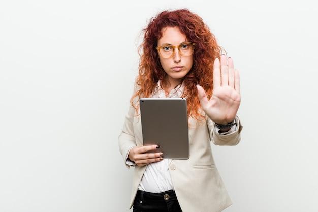 Mujer caucásica joven del pelirrojo del negocio que sostiene una tableta que se coloca con la mano extendida que muestra la señal de stop, previniéndole.