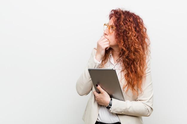 Mujer caucásica joven del pelirrojo del negocio que sostiene una tableta que mira de lado con expresión dudosa y escéptica.
