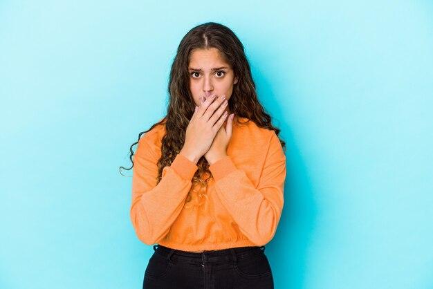 Mujer caucásica joven de pelo rizado aislada cubriendo la boca con las manos mirando preocupado.
