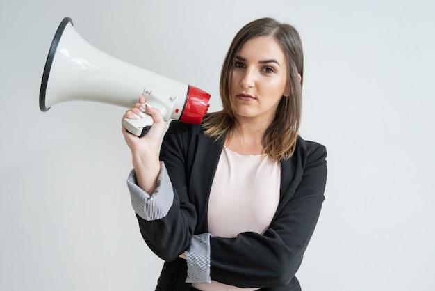 Mujer caucásica joven pensativa que sostiene el megáfono