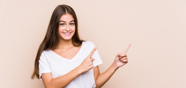 Mujer caucásica joven posando aislado sorprendido señalando con los dedos índices a un espacio de copia.