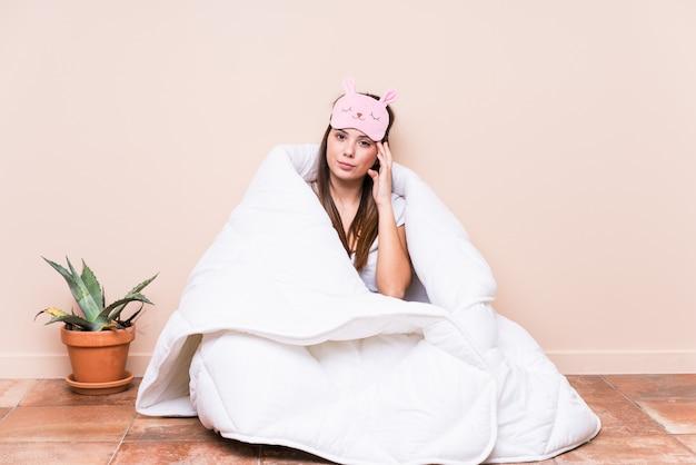 Mujer caucásica joven que descansa con una colcha que señala el templo con el dedo, pensando, centrado en una tarea.