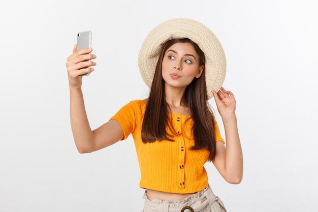Mujer caucásica joven que disfruta del selfie con ella misma aislada en el concepto blanco del viaje del verano.
