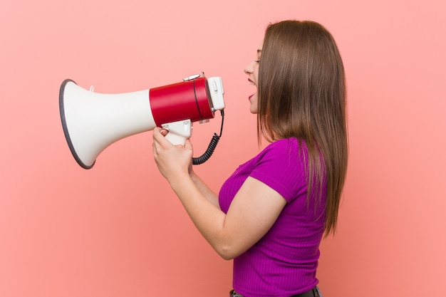 Mujer caucásica joven que habla a través de un megáfono