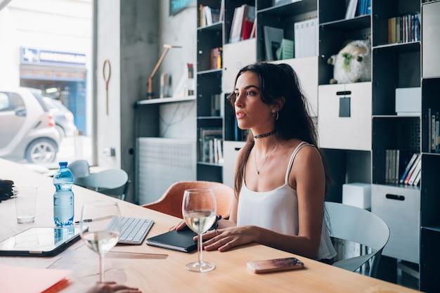 Mujer caucásica joven que interactúa y que se sienta en oficina moderna del co-trabajo