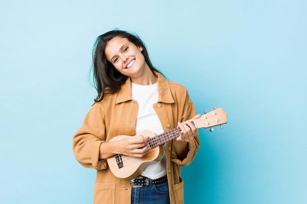 Mujer caucásica joven que juega el ukelele aislado en una pared azul