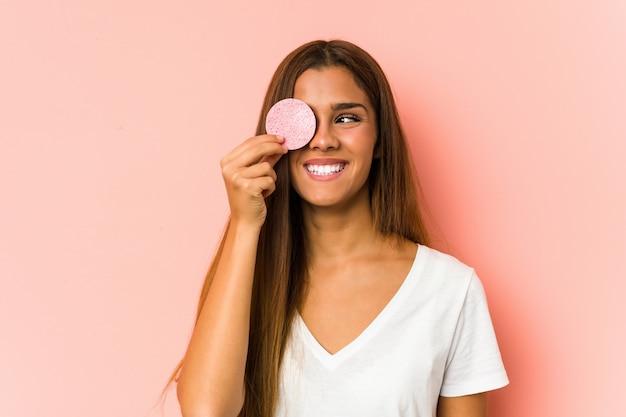 Mujer caucásica joven que limpia su cara con un disco facial aislado