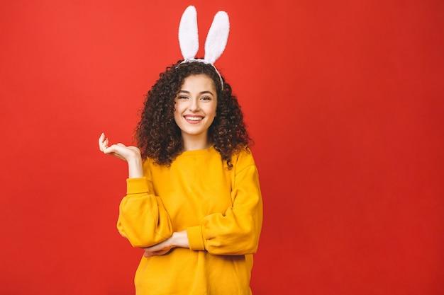 Mujer caucásica joven que lleva los oídos de conejo lindos de pascua sobre fondo aislado rojo mientras que sonríe confiado y feliz.