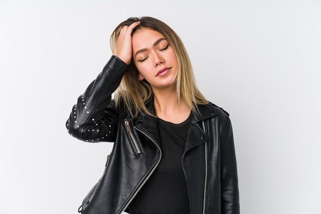 Mujer caucásica joven que llevaba una chaqueta de cuero negra cansada y con mucho sueño manteniendo la mano en la cabeza.