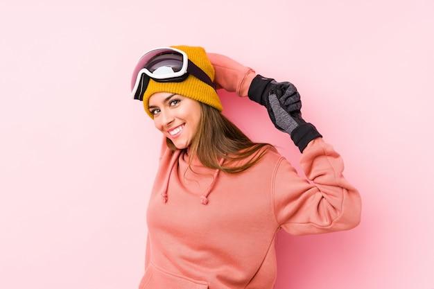 La mujer caucásica joven que llevaba un esquí viste aislado estirando los brazos, posición relajada.