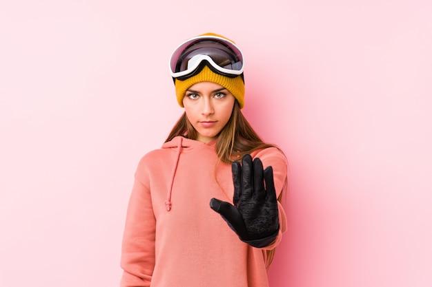 La mujer caucásica joven que llevaba un esquí viste la situación aislada con la mano extendida que muestra la señal de stop, previniéndole.