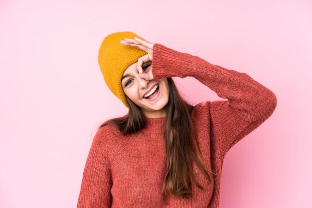 La mujer caucásica joven que llevaba un gorro de lana excitó mantener gesto bien en el ojo.