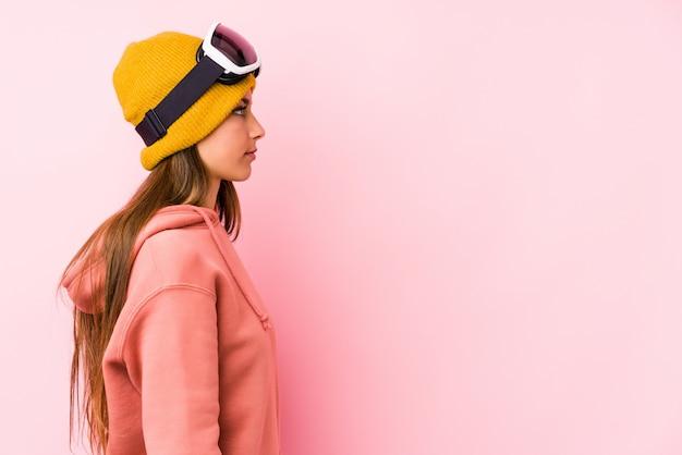 La mujer caucásica joven que llevaba una ropa de esquí aisló la mirada izquierda, pose lateral.