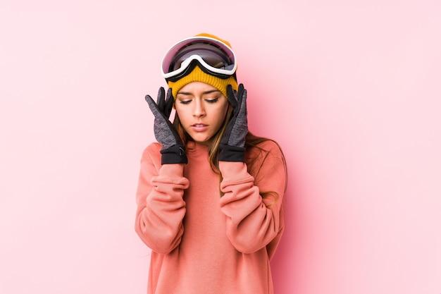 La mujer caucásica joven que llevaba una ropa del esquí aisló tocar los templos y tener dolor de cabeza.