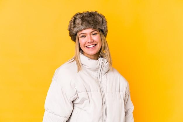 Mujer caucásica joven que llevaba una ropa de invierno aislada feliz, sonriente y alegre.
